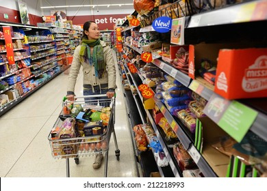LONDON - AUG 18: A shopper browses an aisle at an Asda supermarket on Aug 18, 2014 in London, UK. Asda is the UK's third largest retail chain with 568 stores and an operating income of �£638 million.