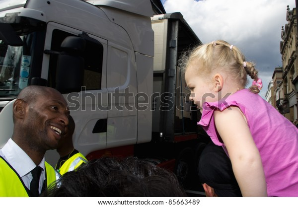 LONDON - AUG 28: black security man smiles at an unidentified blonde child during the  Notting Hill Carnival on August 29, 2011 in London, England. The annual carnival,  has been one of the safest in the history.