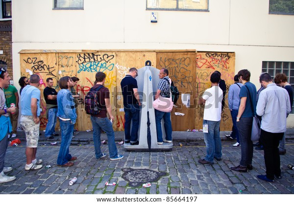 LONDON - AUG 28: men queue up at a open-sky toilet during the  Notting Hill Carnival on August 29, 2011 in London, England.