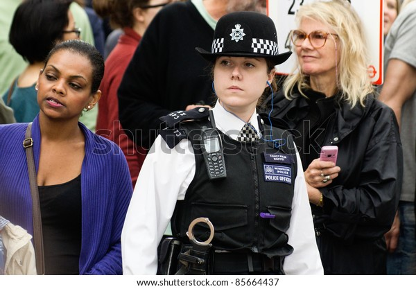 LONDON - AUG 28: policewoman patrols the street of  Notting Hill during the famous annual caribbean  Carnival on August 29, 2011 in London, England.