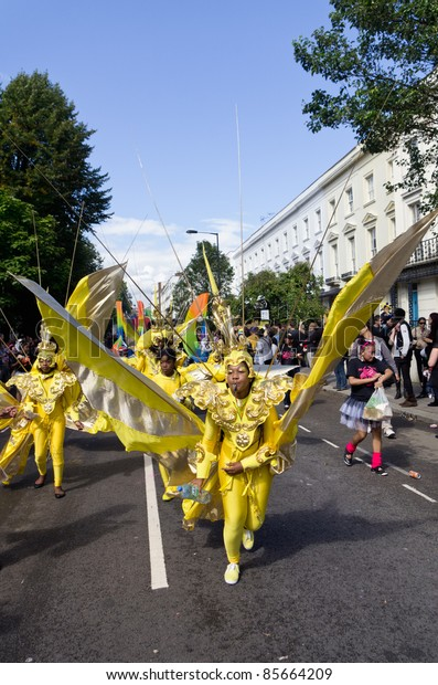 LONDON - AUG 28: yellow dressed performer parades in the Notting Hill Carnival on August 29, 2011 in London, England.