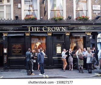 LONDON - AUGUST 1, 2013:  One of the fondest traditions of England is chatting outside a pub on a warm summer evening, as seen in London on August 1, 2013.