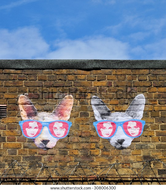 LONDON - AUGUST 1, 2015. Street art on an old brick wall in Hanbury Street, Shoreditch in the Borough of Tower Hamlets, an area renown for its public painting and posters in east London, UK.
