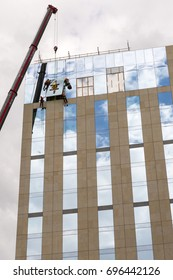 LONDON, AUGUST 15, 2015: Construction workers using a crane to install a pane of glass to the side of a tall building.