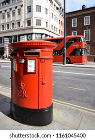 LONDON - AUGUST 15, 2018. Iconic symbols of London; a traditional red roadside double postal piller box and a red Routemaster bus in Piccadilly, central London, UK.
