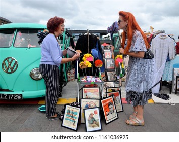 LONDON - AUGUST 18, 2018. Negotiating a hat at the Classic Car Boot Sale, where traders bring their goods in vintage vehicles, located across Granary Square in the King's Cross area of London, UK.