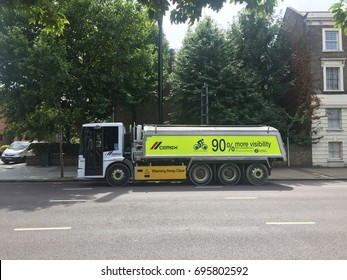 London, August 2017. A cycle friendly lorry operated by Cemex and featuring side boards and extended side and front windows to boost driver visibility is parked on a road in South West London