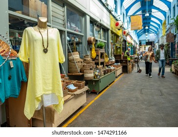 LONDON- AUGUST, 2019: Clothes and craft shops inside Brixton Village, part of Brixton Market- an indoor hall of food stalls, bars and shops from an ethnically diverse background.