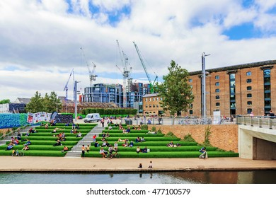 LONDON - AUGUST 22: View of Granary Square with people sitting riverside along the regents canal and the Central Saint Martins university campus in the background on August 22nd, 2016 in London