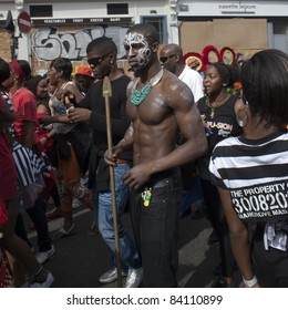LONDON - AUGUST 29: Unidentified man shows his muscular body with other people walking in background, during the Notting Hill Carnival on August 29, 2011 in Notting Hill, London, England.