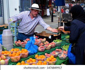 LONDON - AUGUST 3, 2019. A fruit stall holder serves a customer at the Church Street open air market in the Marylebone district of London, UK.