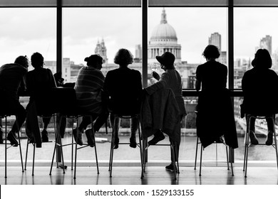 LONDON - AUGUST 9, 2019: Silhouette of a small group of people enjoying the view of London while having some drinks at an elevated bar in the Tate Modern Museum. Monochrome.