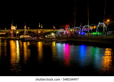 London Bridge at Lake Havasu during Christmas with multi colored lights reflecting off water.