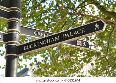 London Buckingham Palace direction signpost near Hyde Park Corner with green tree branches in the background. Direction signpost to British Queen London residence The Buckingham Palace.