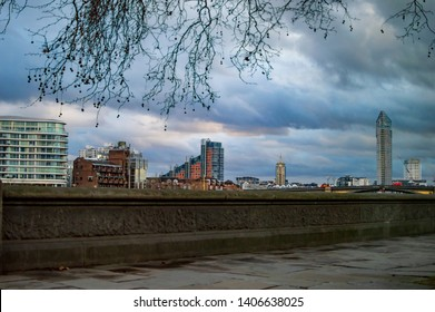 London buildings on the river thames and branches of tree in uk