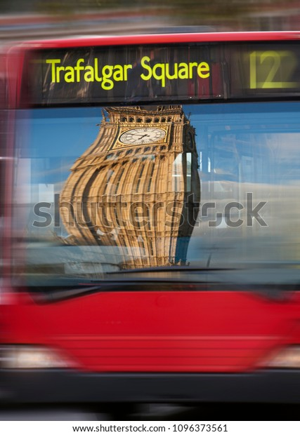 London Bus traveling to Trafalgar Square with a distorted Big Ben reflected in it's window.