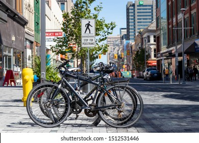 LONDON, CANADA - September 19, 2019: Bikes tied up at bike rack in downtown London, Ontario with a pedestrian crossing behind.
