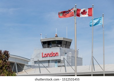 "LONDON, CANADA - September 19, 2019: London International Airport, Air Traffic Control Tower above terminal with ""London"" sign on it and flags waving in-front."