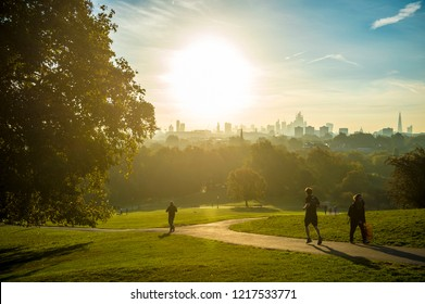 LONDON - CIRCA OCTOBER, 2018: Joggers pass in front of a sunrise skyline view of the city.