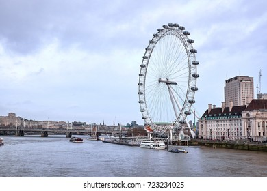 LONDON CITY - DECEMBER 24, 2016: Gigantic London Eye standing on the quay of the River Thames north bank in cloudy weather