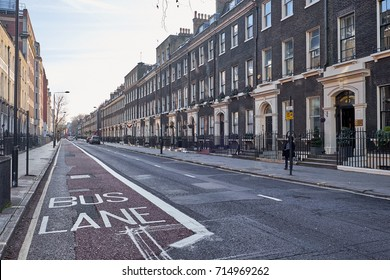 LONDON CITY - DECEMBER 26, 2016: Woman walking on an empty Gower Street with a marked bus lane, on Christmas
