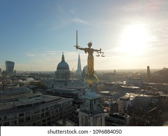 London city landscape drone view with golden lady justice statue in front of glaring sunshine
