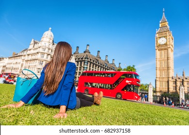 London city lifestyle woman relaxing in Westminster summer park, red bus and big ben tower. Urban girl outdoors.