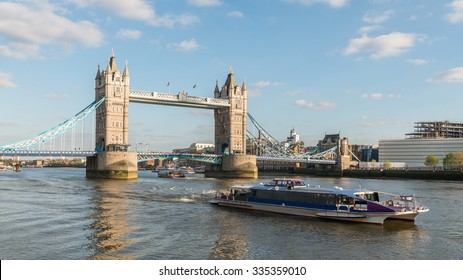 London City, Tower Bridge (Symbol of Skyline Landmark) and Thames Clippers cruise under Clear Blue Sky at Sunset in Summer. River Bus Boat Commuter and Tourist service on the River Thames, England, UK