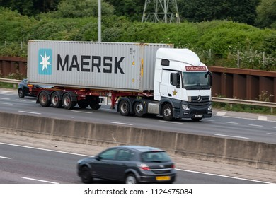 LONDON COLNEY, UK - JUNE 28, 2018: Lorry carrying Maersk shipping container in motion on British motorway M25