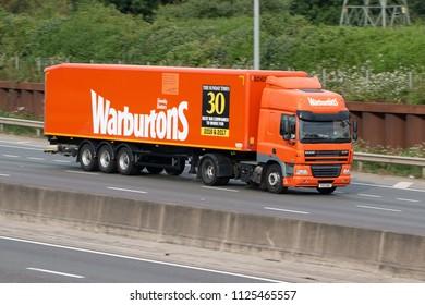LONDON COLNEY, UK - JUNE 28, 2018: Orange lorry belonging to the British baking firm Warburtons in motion on motorway M25