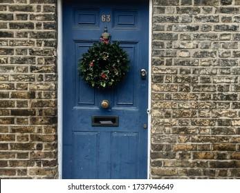 London colour photo of door facade brick wall decorative traditional Christmas wreath, United Kingdom