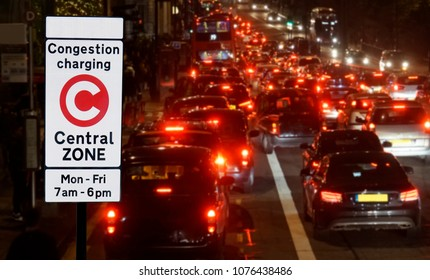 London Congestion Charge Zone Sign over night view of traffic jam, vehicles slow bumper to bumper.