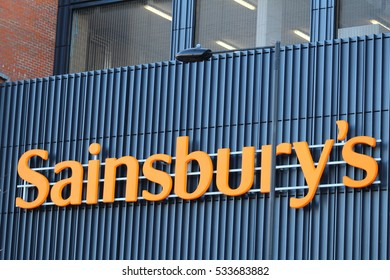 London, December 2016. A sign on the exterior of a branch of Sainsbury's, a UK supermarket chain selling groceries, clothes and household goods.