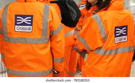 London, December 2017. Workers at the site of the future Farringdon station for London's Crossrail rail project are seen wearing orange hi vis safety jackets bearing the 'Crossrail' logo & branding.
