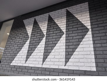 LONDON - DECEMBER 23, 2015. Painted directional graphics on a brick wall at the Broadway Shopping Centre in the Borough of Hammersmith and Fulham, west London, UK.