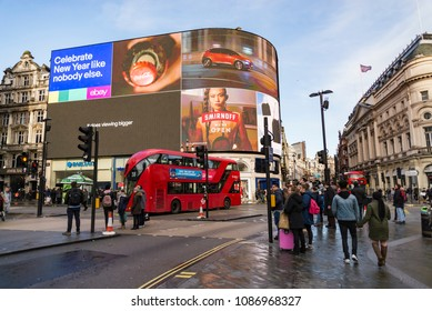 LONDON - DECEMBER 29: view of Piccadilly Circus  with buses and crowds on December 29, 2017 in London UK. Advertisements have been here for at least 20 years and are considered symbols of famous