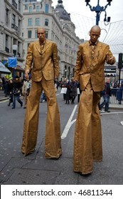 LONDON - DECEMBER 5: Two golden men on stilts at Shop West End VIP (Very Important Pedestrians) Day in London West End, December 05, 2009 in London, England.