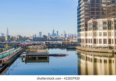 London Docklands low docks property train Thames view with downtown, cucumber and city center real estate buildings suburbs