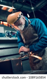 london, england, 02/02/2018, Young industrial metal working apprentice worker angle griding,learning various metal working skills in an industrial factory setting. Apprentice schemes in england.