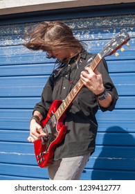 london, england, 04/04/2018 A rock and roll heavy metal concert guitarist with long hair rocking out playing a red lead guitar on the street against shutters on a high street. Busking street art enter