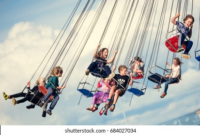 london, england, 05/05/2017 Children swinging in the air on a chair swing ride carousel, swing carousel. Children having fun on a fairground ride.