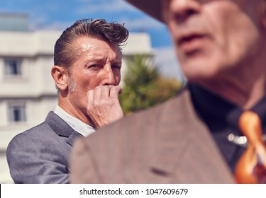 london, England, 05/05/2017, A stylish retro vintage teddy boy elvis style 1950s fashionable man with a quiff, smoking a cigarette at a vintage event..