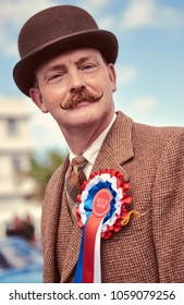 london, England, 05/05/2017, A stylish retro vintage fashionable gentleman in a brown blazer, rosette, hipster moustache and a bowler hat at a vintage event at the midland hotel.