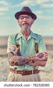 london, England, 05/05/2017, A stylish retro vintage fashionable elder hipster man, with cuban style  and tattoos posing on a warm empty beach.Best dressed award.