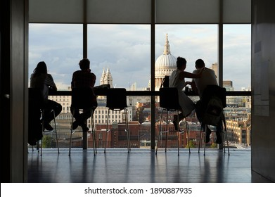 London England; 08,28,2015: Two couples gaze out over the River Thames and St. Paul's Cathedral from the Tate Gallery Bar's observation deck selective focus
