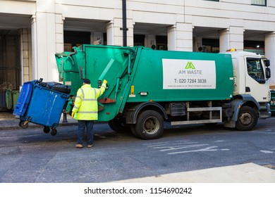 LONDON, ENGLAND - 10 APRIL 2017 - Garbage collector loads trash into his truck in London, England on April 10, 2017