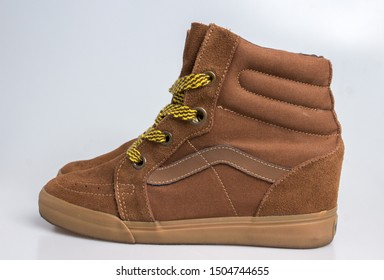 London, England, 10/09/2019 Brown Vans hi top sk8 skate shoes or boots with bright yellow laces shot in a studio with a white background isolates shoes Clean looking classic style retro vintage style