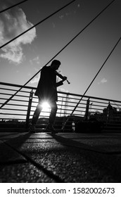 London, England: 11 05 2019: silhouette of a young man playing the violin in the middle of a bridge during a sunset