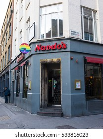 London, England - 11 December 2016: Entrance of Nando's Soho restaurant a popular spicy chicken restaurant chain with rainbow flag on its symbol due to the strong gay and LGBT community living in Soho
