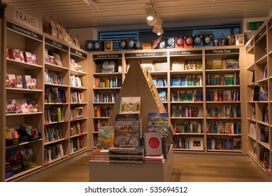 London, England - 11 December 2016: Interior of a modern bookshop with wooden shelves full of books. Section of travel books and guides.